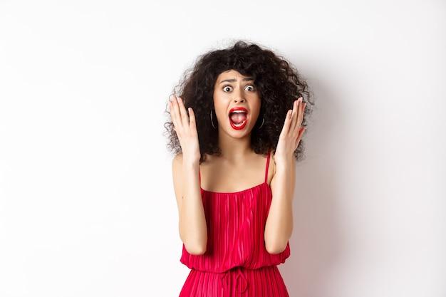 Vrouw schreeuwt in paniek, draagt een rode jurk en schreeuwt naar de camera met een angstig gezicht, staande op een witte achtergrond. kopieer ruimte