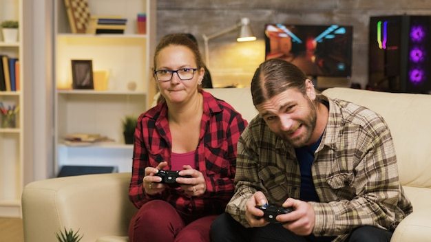 Vrouw schreeuwt tegen haar vriendje na verlies bij videogames zittend op de bank. man en vrouw die videospelletjes spelen.