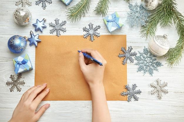 Vrouw schrijft brief aan de kerstman aan houten tafel