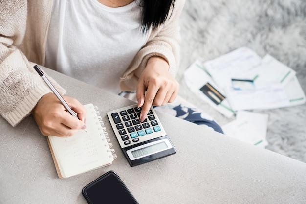 Vrouw schrijft haar schulduitgaven berekenen met rekenmachine