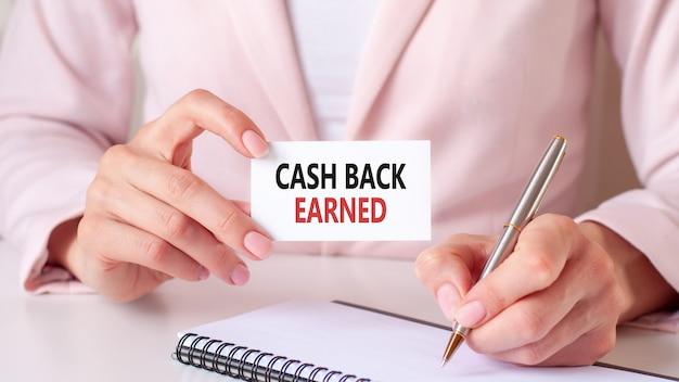 Vrouw schrijft in een notitieboekje met een zilveren pen en hand met kaart met tekst: geld terug verdiend.