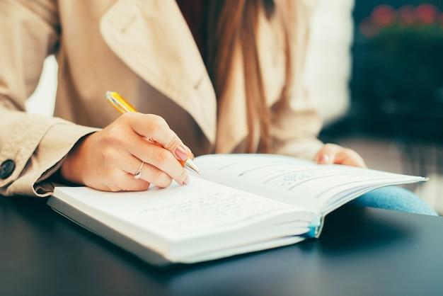 Vrouw schrijft in haar planner aan een tafel