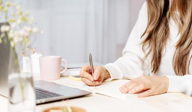 Vrouw schrijft in notitieblok op bureau met laptop