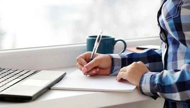 Vrouw schrijft in notitieblok