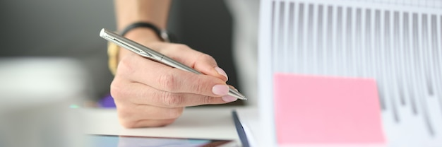 Vrouw schrijft met balpen in documenten met grafieken en diagrammen aan tafel op kantoor