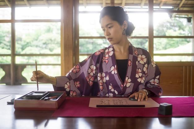 Vrouw schrijft met inkt op japans papier