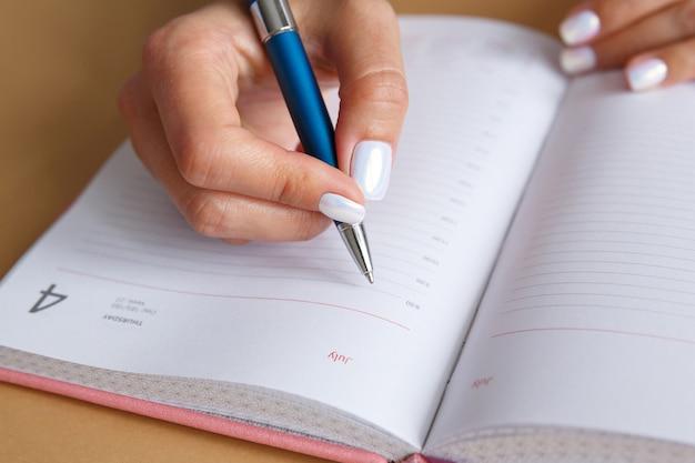Vrouw schrijft met zilveren metalen pen in dagboek dagelijkse planning zakenvrouw maakt werkdagplan