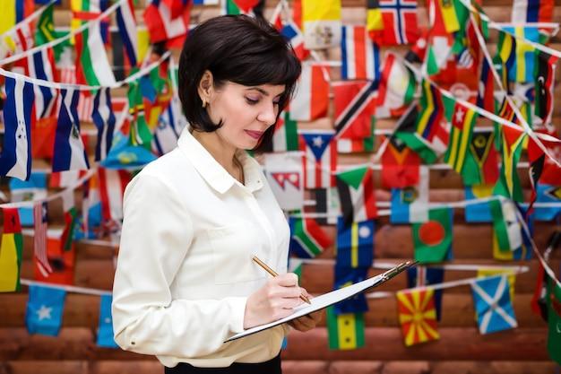 Vrouw schrijft op papier tegen de achtergrond van een muur gemaakt van vlaggen van de wereld