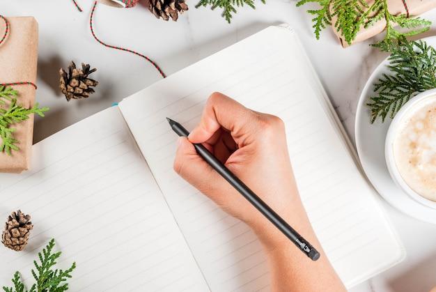 Vrouw schrijft wensen of takenlijst in notitieblok, koffiemok, kerstcadeau of huidige doos, versierd met kerstboomtakken, dennenappels, rode bessen, op witte marmeren tafel, kopie ruimte bovenaanzicht