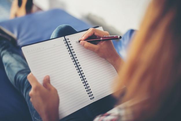 Vrouw schrijftafeltje in een notebook op de bank