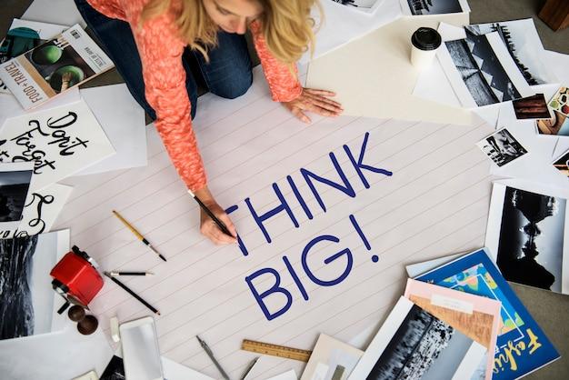 Vrouw schrijven denk groot op een papier