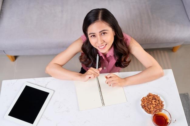 Vrouw schrijven in leerboek, bekijken van bovenaf