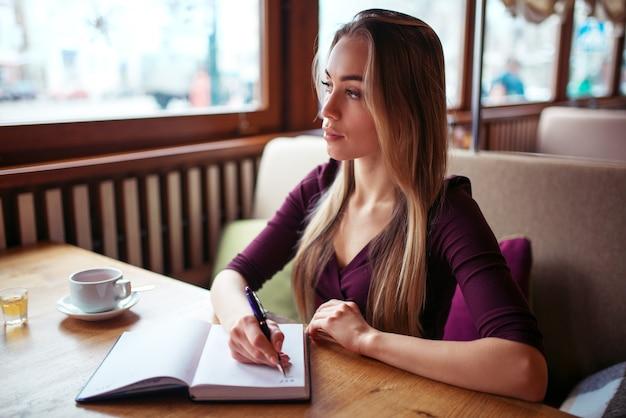 Vrouw schrijven in notitieblok in restaurant.