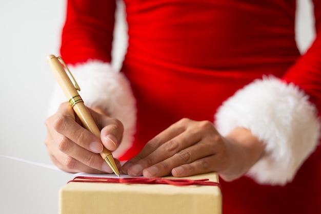 Vrouw schrijven notitie voor kerstcadeau