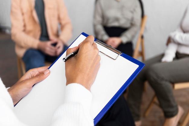 Vrouw schrijven op klembord tijdens een groepstherapie sessie