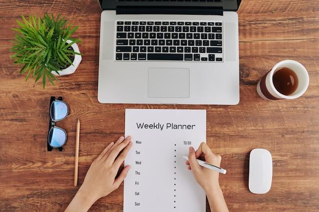 Vrouw schrijven wekelijkse planner