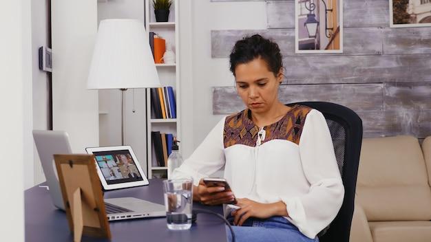 Vrouw scrollen op haar smartphone tijdens het werken vanuit kantoor aan huis.