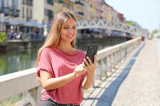 Vrouw scrolt berichten op smartphone-app om te chatten in milaan, italië