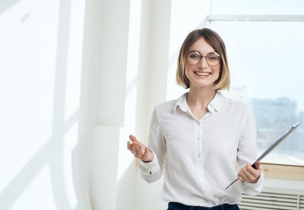 Vrouw secretaresse in wit overhemd map voor papieren copyspace office