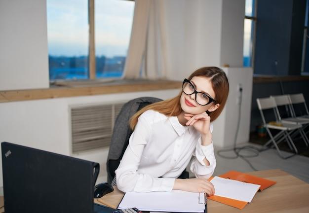 Vrouw secretaresse zit aan haar bureau documenten kantoor laptop