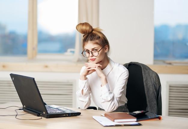 Vrouw secretaresse zittend aan werktafel of laptop adressen technologisch werk