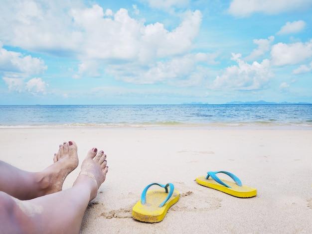 Vrouw selfie op blote voeten en gele sandalen op het strand.