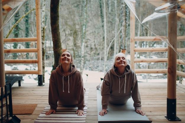 Vrouw senior en jonge ontspannen op glamping camping tent buiten. vrouwen familie bejaarde moeder en jonge dochter doen yoga en meditatie binnen. modern zen-achtig vakantielevensstijlconcept.