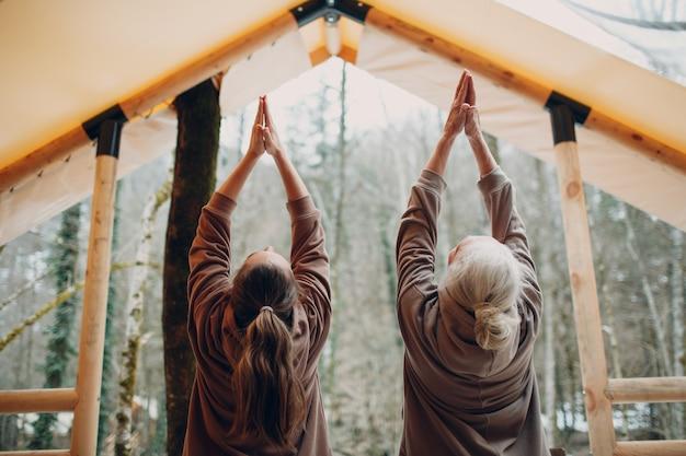 Vrouw senior en jonge ontspannen op glamping camping tent vrouwen familie bejaarde moeder en jonge dochter doen yoga en meditatie binnen moderne zenlike vakantie levensstijl concept