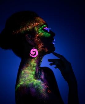 Vrouw sensuele poseren in fluorescerende verf make-up