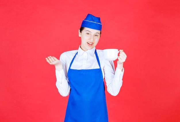 Vrouw serveerster in uniform staan en houden een kopje op de rode muur.