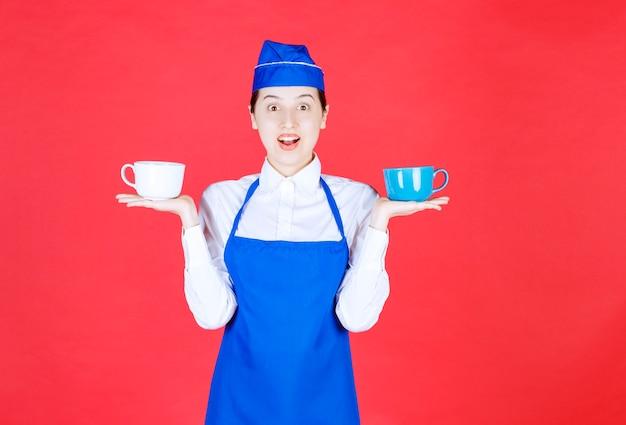 Vrouw serveerster in uniform staan en houden van kleurrijke kopjes op rode muur.
