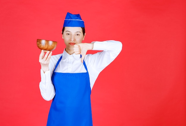Vrouw serveerster in uniform staande met een houten kom en duim naar beneden tonen.