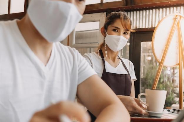 Vrouw serveerster serveert een drankje aan de klant met masker op het gezicht