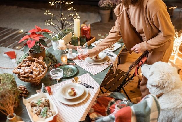 Vrouw serveert en decoreert een feestelijke eettafel op kerstavond buiten op het terras