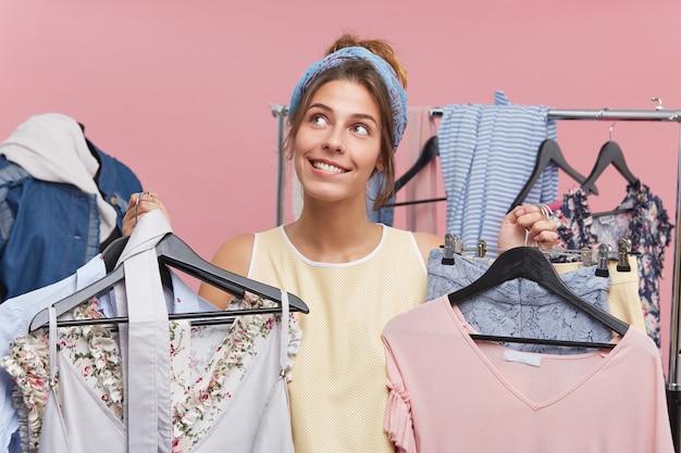 Vrouw shopaholic is in boetiek en kiest veel outfits, kijkt met een dromerige uitdrukking omhoog, niet wetend welke kleding ze moet kiezen voor een date met een vriendje. vrolijke vrouwelijke koper van modieuze kleding