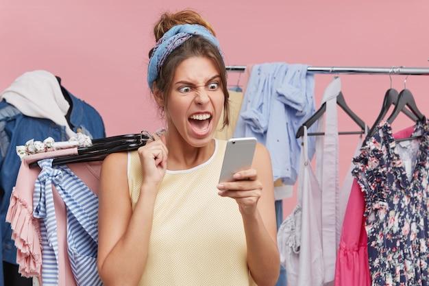 Vrouw shoppaholic winkelen in winkelcentrum, hangers van stijlvolle kleding vasthouden, schreeuwen van woede en shock, met behulp van online bankieren app op mobiel, gefrustreerd dat geld niet beschikbaar is op bankrekening