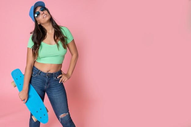 Vrouw skater stijl poseren op lege roze muur met copyspace