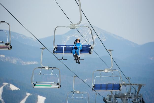 Vrouw skiër rijden tot aan de top van de berg