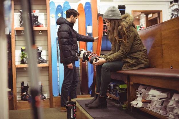 Vrouw skischoen in een winkel selecteren