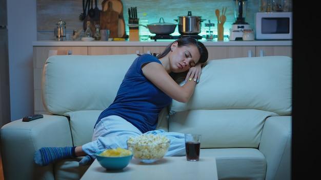 Vrouw slaapt op een bank voor tv terwijl ze naar een verveelde film kijkt. vermoeide, eenzame slaperige dame in pyjama die in slaap valt terwijl ze op een gezellige bank in de woonkamer zit en 's nachts de ogen sluit