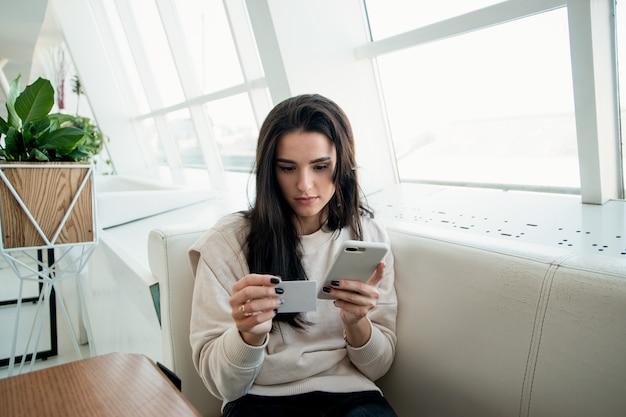 Vrouw slaat het telefoonnummer op van de man die ze leuk vindt. liefde op het eerste gezicht-concept. vrouw ontmoette man in een coffeeshop en vroeg hem om een telefoonnummer. lichte witte kamer op de achtergrond.
