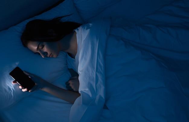 Vrouw slapen met smartphone in bed