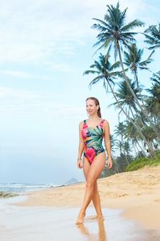 Vrouw slentert langs de oceaan kust