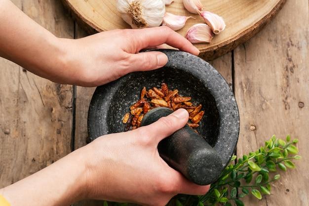Vrouw slijpen peper met stamper en vijzel
