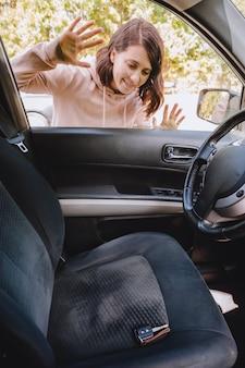 Vrouw sloot de auto en vergeet de sleutels binnen. kopieer ruimte
