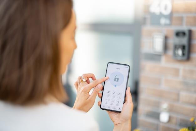 Vrouw sluit de deur of zet het huisalarm aan met een mobiele telefoon. apparaat met lopend programma voor huisbeveiliging. innovatieve technologieën in huisbeveiliging