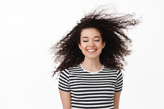 Vrouw sluit ogen en glimlach gelukkig, wind waait op haar gezicht als krullende haarlokken vliegen in de lucht, staande in t-shirt op wit
