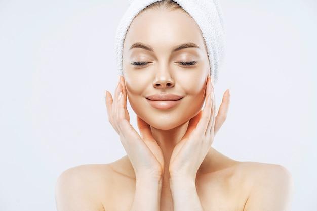 Vrouw sluit ogen, staat halfnaakt met omwikkelde handdoek op hoofd
