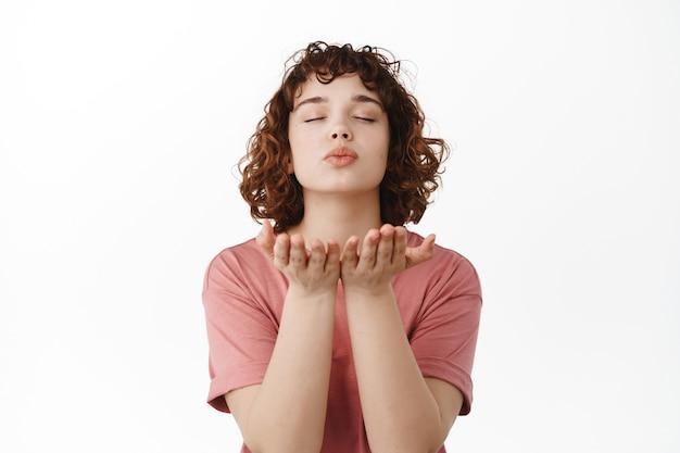 Vrouw sluit ogen, verzendt luchtkus, blaast mwah zoenen in open handen in de buurt van lippen, staand in t-shirt op wit