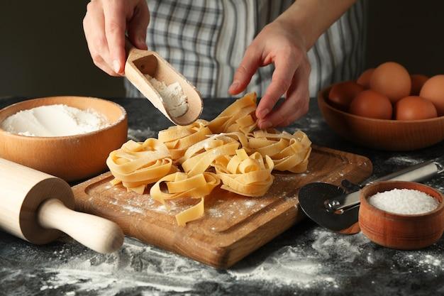 Vrouw smakelijke pasta koken op donkere tafel